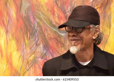 London-April 4 2017 : Malaysian painter and abstract expressionist in front of one of his masterpiece painting 'Art Of War' during his solo arts exhibition Segerak in London at the Asia House, London