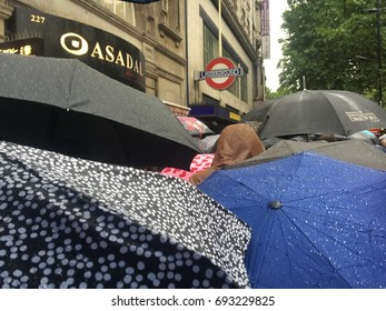 London-August 9 2017 : Commuters queue in the rain in front of a the Underground station in Holborn during rush hour. Rainy weather often cause tube service disruptions around London.