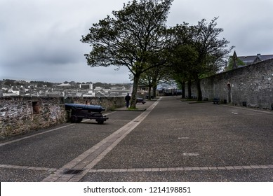 Londonderry, Northern Ireland - April 24, 2011: A man walks past cannons located on the city wall in Londonderry. The city is often referred to as Derry.