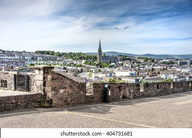 Londonderry, Northern Ireland: Panorama view skyline of Derry with St. Eugene's Cathedral near Free Derry Corner, city wall, skyline, horizon and blue sky in the background. June 23, 2015