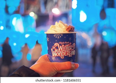 London/England- December,2017: A hand holding a cup of hot chocolate topping with whip cream with blurred background of the Hyde Park Winter wonderland festival in London
