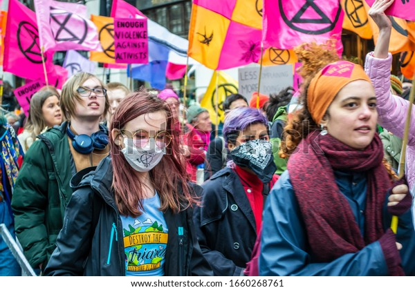 LONDON/ENGLAND – FEBRUARY 22 2020: Extinction Rebellion protester wearing a surgical mask during the February 2020 March along with Parents 4 Future, amid the Coronavirus outbreak