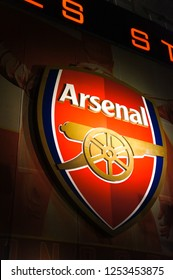 LONDON,ENGLAND - UK - DEC 6, 2018  : Red plaque logo banner with the big gun of Arsenal Football club on wall light at Emirates Stadium in London,UK.Arsenal is the top team favour in Premier league.