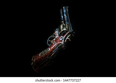 LONDON,ENGLAND,DECEMBER 10th,2018: pistol revolver isolated on black background. Jeweled revolver, customized .357 Magnum with red gold, red enamel and diamond decoration. Part of the Royal Armouries.