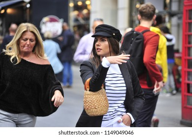 London,England/United Kingdom- 09/15/2017: An attractive brunette walks along the streets of Central London with her mother.