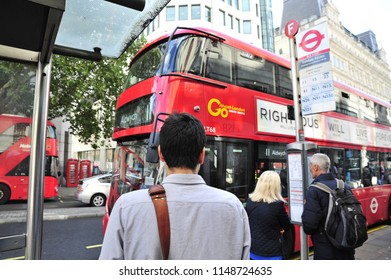 London,England/United Kingdom- 09/15/2017: Passengers in London wait to board a bus on a cold afternoon.