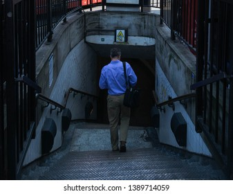 London/Enland/- 08-17-2018: Well dressed adult entering dark, spooky subway that has a secret and might be dangerous. Darkness, void, mystery concept.