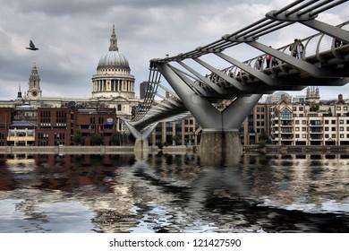LONDON-MAY 28 :People walking across a footbridge Millennium Bridge. Background is St Paul's cathedral in London. Bridge was opened 10 June 2000. View on May 28, 2012