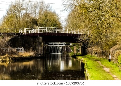 The London-Rugby railway bridge crossing over the Grand Union Canal in Whilton Locks. Landscape looking up the waterway, with distant view to the closed lock gates. Northamptonshire. England.