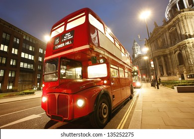 London's iconic Routemaster Bus at dusk and St Paul's Cathedral is in the background.