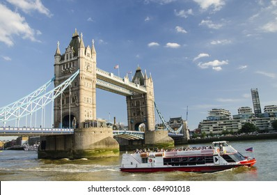 London's Tower Bridge cross River Thames with cruise ships for tourism bathed on a bright Summer's day.Famous place against blue sky in London, England.