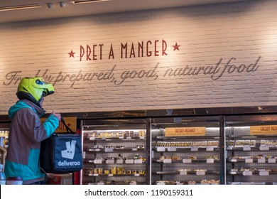 LONDON-SEPTEMBER, 2018: Pret a Manger store interior and a Deliveroo food delivery service doing a pick up,