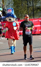 London/UK 04-13-14 Virgin Money London marathon 2014. Barry Julyan (7347) looks relieved he only has a few yards left to run. But is oblivious to the fact Paddington bear is closing on him fast