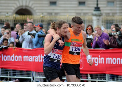 London/UK 04/23/17 Virgin London Marathon 2017 One runner helps another to the finish line just a few yards away