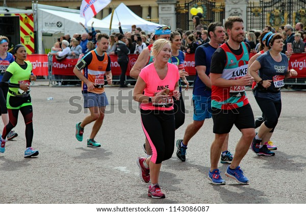 London/UK 04/23/17 Virgin London Marathon 2017 A group of amateur runners pass Buckingham palace with less than 200 yards to go