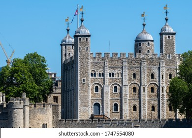 London.UK- 05.30.2020:  view of the Tower of London by the north bank of the Thames river with the Union Jack flying on one of the towers. A popular tourist attraction which houses the Crown Jewels.