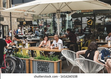 London/UK - 22/07/18: people in a sitting area of the Crêpeaffaire cafe on the Spitalfields Market. It is a traders' market as well as a food and art market located in Spitalfields, Central London