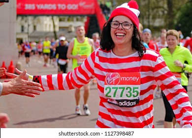 London/UK 4/22/12 Virgin London Marathon 2012. Yards from the finish by Buckingham palace a delighted Karen Hodgson in Where's Wally fancy dress celebrates by high fiving the watching supporters