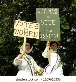LONDON/UK- JUNE 10th 2018: Two women dressed in historic outfits and carrying VOTES FOR WOMEN banners, attend the folk festival in barking, east London, to celebrate 100yrs of female suffrage.
