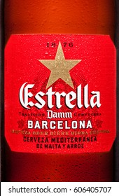 LONDON,UK - MARCH 21, 2017 : Bottle label of Estrella Damm beer on white background with reflection, Estrella Damm is a pilsner beer, brewed in Barcelona.
