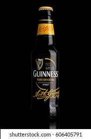 LONDON,UK - MARCH 21, 2017 : Bottle of Guinness foreign extra beer on black background.Guinness beer has been produced since 1759 in Dublin, Ireland.
