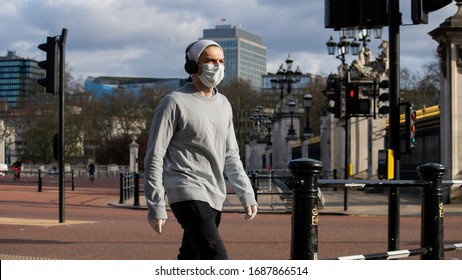 London/UK - March 29th 2020: Man wearing a mask walking near an empty Victoria Memorial with the gates of Buckingham Palace in the background