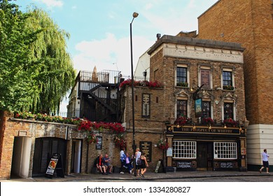 London,UK-August 13th 2016:View of Wapping Wall street with the Prospect of Whitby-a historic public house on the banks of the Thames at Wapping,site of the oldest riverside tavern, dating from 1520