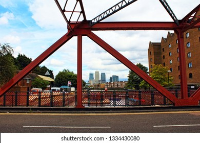 London,UK-August 13th 2016:Wapping Wall road and the Shadwell Basin Bridge -red steel bascule bridge at the edge of Shadwell Basin in Wapping, East London,Canary Wharf skyscrapers in the background
