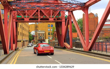 London,UK-August 13th,2016:Red sports car moving on red Shadwell Basin Bridge at Wapping Wall road towards the Prospect of Whitby -historic public house in the East End of London.