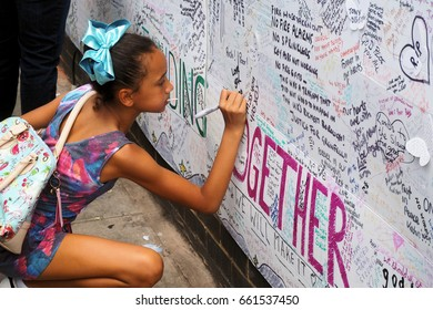 London.UK.June 17, 2017.A young girl writes on the memorial wall for the victims of the Grenfell Tower tragedy.