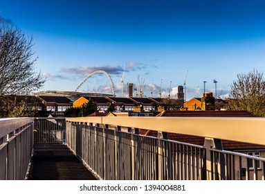 London,UK,North Circular Road,Circa February 2019.Crossing a bridge over the busy arterial road you catch a glimpse of the Wembley Stadium Arch set against a dark blue sky, after heavy rain