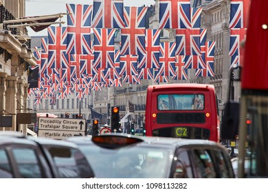 London/United Kingdom - 05 20 2018: English flags, taxis and a red bus on Oxford Street