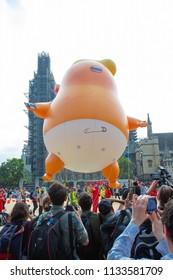 """London/United Kingdom - July 13, 2018: Donald Trump's visit to England is met with protests and a blimp flying over London. Big Ben shrouded in scaffolding serves as a backdrop to """"Angry Trump Baby"""""""