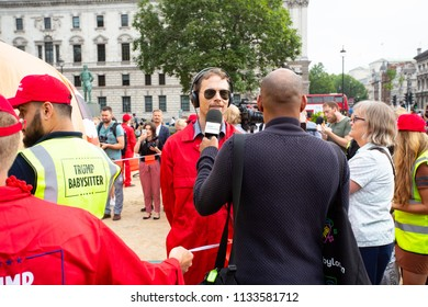 """London/United Kingdom - July 13, 2018: Donald Trump's visit to England is met with protests and a blimp flying over London's Parliament Square.  A """"Trump Babysitter"""" is interviewed on London radio."""