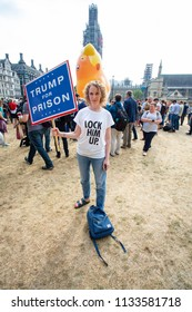 London/United Kingdom - July 13, 2018: Donald Trump's visit to England is met with protests and a blimp flying over London. A protestor holds a sign proclaiming Trump should be in prison.