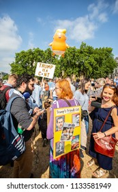 London/United Kingdom - July 13, 2018: Donald Trump's visit to England is met with protests and a blimp flying over London's Parliament Square.  Protestors hold signs protesting Trump.