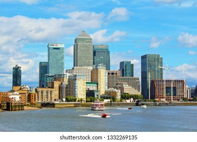 London,United Kingdom,August 13th 2016;View of Canary Wharf from the west with Thames River against nice blue sky with white clouds.Busy financial area filled with striking skyscrapers