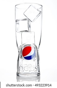 LONDON,UNITED KINGDOM-OCTOBER 03, 2016: Original empty pepsi cola glass with ice cubes. Pepsi is a carbonated soft drink that is produced and manufactured by PepsiCo. Created and developed in 1893.
