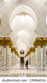 Lone Arabian woman along the Interiors of Sheikh Zayed Mosque, Abu Dhabi, United Arab Emirates