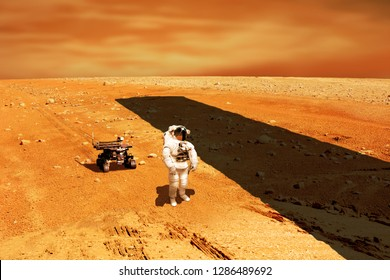 A lone astronaut with a rover, looks up at a huge monolith silhouetted against the sun while exploring a barren planet similar to Mars. - Elements of this image courtesy of NASA.