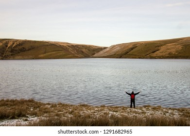 A lone backpacker with arms outstretched standing on the edge of a reservoir looking out on bleak moorland in winter. Elan Valley, Wales. UK.