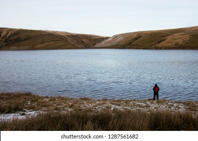 A lone backpacker standing on the edge of a reservoir looking out on bleak moorland in winter. Elan Valley, Wales. UK.