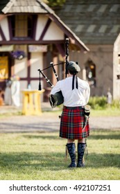 A lone bagpiper in kilt playing outside