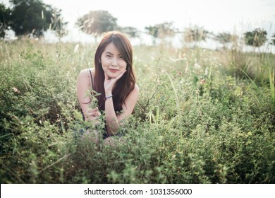 A lone beautiful young lady with hands on the cheek amid bushes at shrubland.