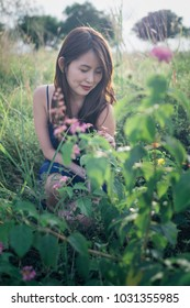 A lone beautiful young lady in tight fitting blue dress and curly long brown hairs squat down admiring flowers outdoors.