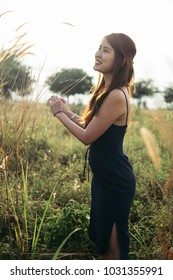A lone beautiful young lady in tight fitting blue dress both hands holding stalk of dandelion