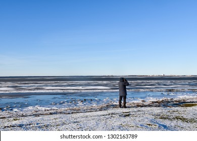 Lone birdwatcher looking over an icy coast at the swedish island Oland
