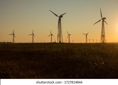Lone black silhouettes of wind turbines. Renewable energy generation. Evpatoria, Crimea.