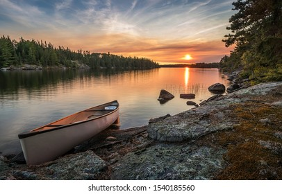 A lone canoe on shore at a peaceful lake at sunset. The odd colored clouds in the background are from a forest fire in Northwest Ontario, Canada in the summer of 2018.