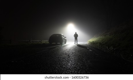 A lone car, parked on the side of the road, underneath a street light, with a hooded figure, on a spooky, scary, rural, country road. On a foggy winters night